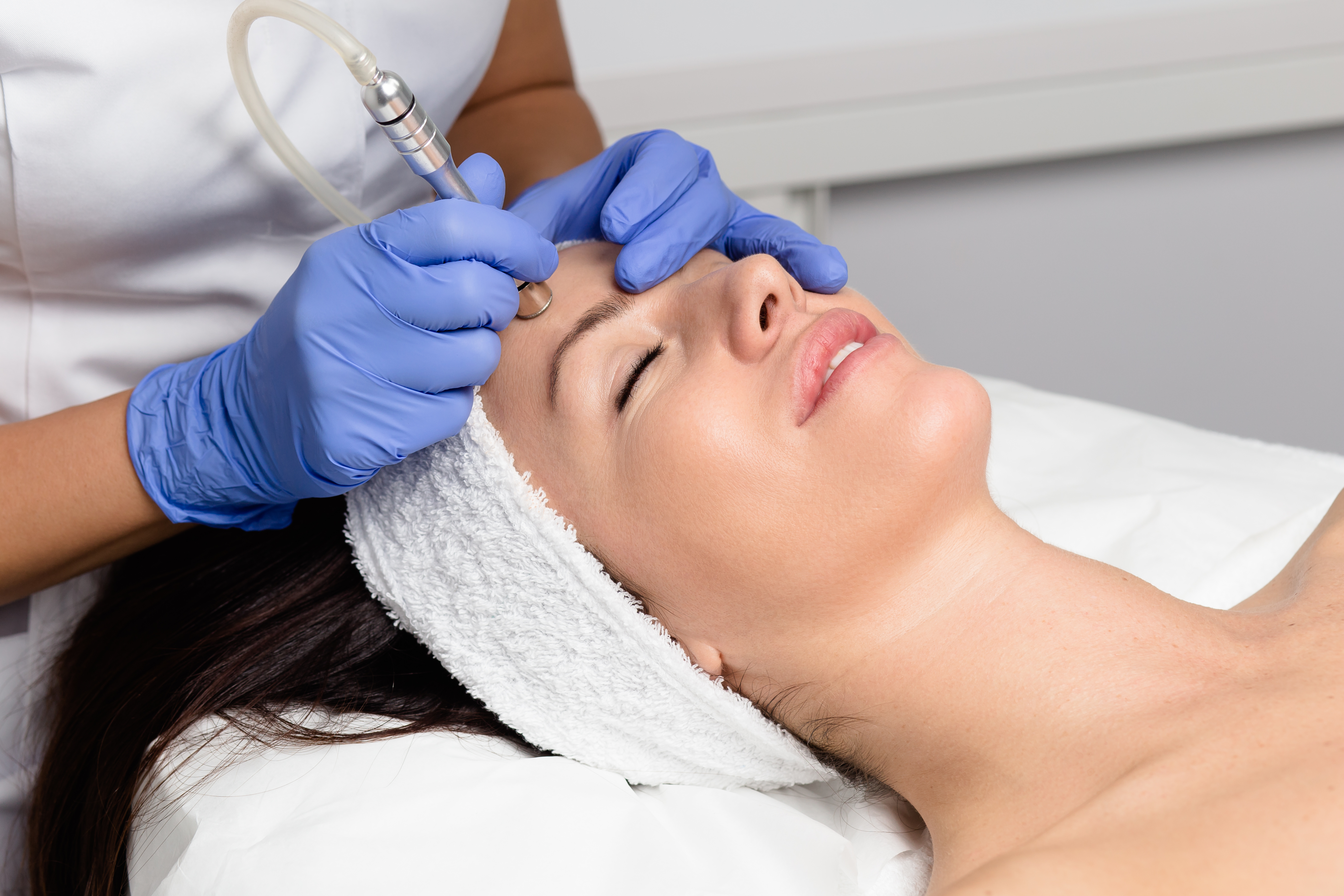 Brown haired girl receiving microdermabrasion treatment in a clinic